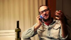 Drunk man talking on cellphone and drinking wine by the table HD Stock Footage