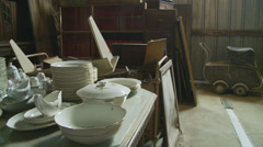 Plates, cups & old pram in French barn Stock Footage