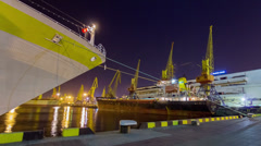 Panning timelapse of white cruise liner Hamburg docked in port with docked cargo Stock Footage