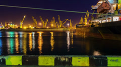 Motion timelapse of big cruise liner docked in port with port cranes unloading Stock Footage