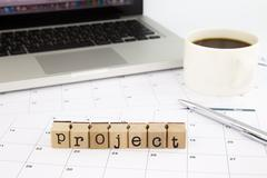 project wording, calendar and laptop on office table - stock photo