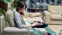 Young woman with laptop computer sitting on sofa at home HD Stock Footage
