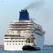 Stock Photo of tugboat while accurately manoeuvre the cruise ship out of the port city
