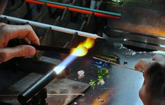Glazier with gas torch lit while shaping glass Stock Photos