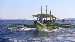 Green motor boat floats on the sea near the island of Coron, Philippines - stock footage