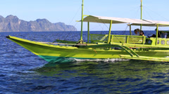 Green motor boat floats on the sea near the island of Coron, Philippines Stock Footage