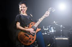Woman guitar player during concert - stock photo