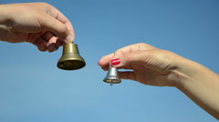 Male and female hands jingle with silver bronze bell on blue sky Stock Footage