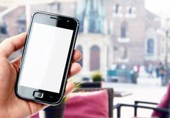 Hand holding blank screen smartphone on blurred background with city cafe Stock Photos