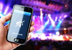Stock Photo of hand holding smartphone with mute sound on the screen during concert