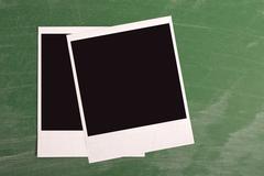Stock Photo of polaroid photo frame on green chalkboard