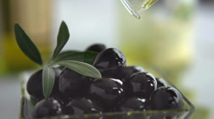 Extra Virgin Olive Oil Pouring on Black Olives - stock footage