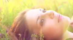 Beautiful Girl Lying on the Meadow and Dreaming Stock Footage