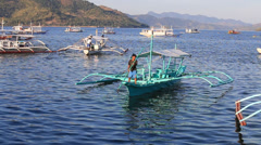 Blue motor boats with a man floats on the sea in island of Coron, Philippines Stock Footage