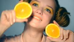 Beautiful joyful teen girl takes juicy oranges - stock footage