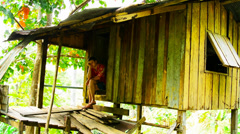 Sad young man sitting by the door in a hut Stock Footage