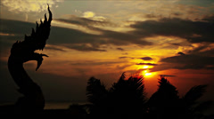 Time lapse of dragon statue on background of sea and orange sunset Stock Footage