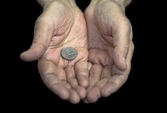 Poverty. Old hands with a single coin of 25 cents - stock photo