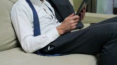 Businessman listening to music on his tablet and relaxing on the sofa after work Stock Footage