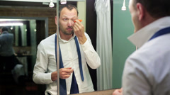 Man applying an eye cream and standing before the mirror Stock Footage