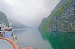 Cruise ship heading into a misty fjord Stock Photos
