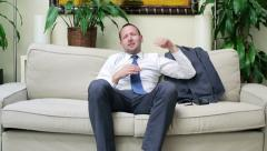 Businessman coming back from work and sitting on the sofa Stock Footage