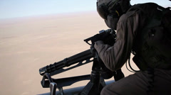 War in Afghanistan - Helicopter Door Gunner firing on Enemy Positions Stock Footage