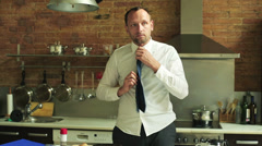 Young businessman tying his tie and finishing breakfast in the kitchen Stock Footage