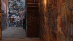 Wide view of urban alley way covered in graffiti Stock Footage