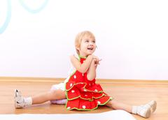 cheerful little girl in red apron - stock photo