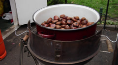 Roasting sweet chestnuts, cooked nuts, street vendor, hot food Stock Footage