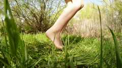 A bare foot of little girl dancing on the green grass Stock Footage