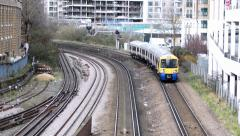 London two trains pass by underground and overground train Stock Footage