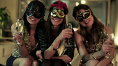 Attractive women in masks holding glasses of champagne and smiling to the camera Stock Footage