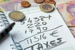 agenda with tax and foreign currency - stock photo