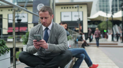 Businessman sitting on street bench and finish texting on cellphone Stock Footage