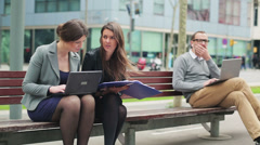 Businesspeople working on laptop and checking documents in street bench Stock Footage