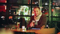Man toast beer and looking to the camera in pub, steadycam shot Stock Footage