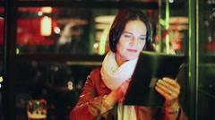 Woman drinking beer and looking on tablet in pub, steadycam shot Stock Footage