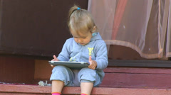 Little girl sitting on the steps and looking Tablet PC Stock Footage