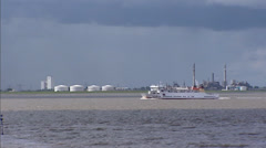 Skyline Dutch industrial area Aldel Delfzijl at Dollart Bay + ferry boat Stock Footage