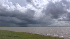 View from German side at Dutch Coast, storm clouds above Dollard bay Stock Footage