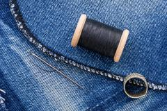 Roll of black thread and jeans Stock Photos