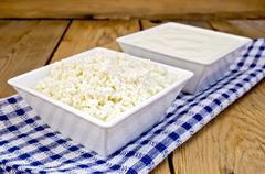curd and sour cream in bowls on board with napkin - stock photo