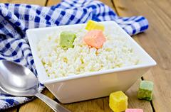 Curd with colored sugar and spoon on board Stock Photos