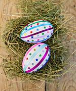 Easter eggs with ribbons and sequins on board Stock Photos