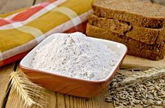 Flour rye in bowl with bread on board Stock Photos