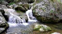 Pure fresh water waterfall running over mossy rocks in the forest Stock Footage