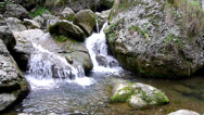 Stock Video Footage of Pure fresh water waterfall running over mossy rocks in the forest