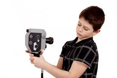 young boy with old vintage analog 8mm camera - stock photo